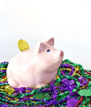 mardigras: Mardi Gras piggy pank on a pile of Mardi Gras beads and coins Stock Photo