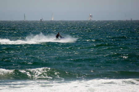 personal watercraft: Jet skier riding the pacific ocean waves in Huntington Beach