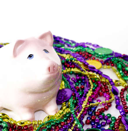 carnivale: Mardi Gras piggy pank on a pile of Mardi Gras beads and coins Stock Photo