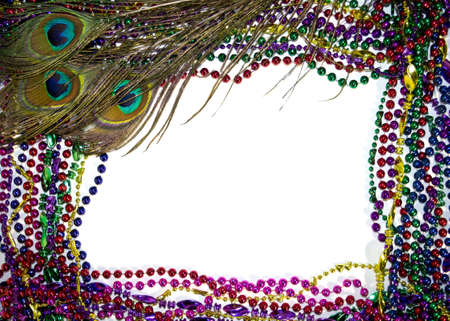 Colorful peacock feathers on a bed of Mardi Gras beads