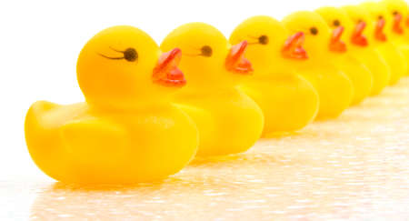 Yellow rubber ducks lined up in a row Stock fotó