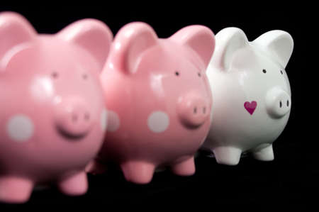 Three little piggy banks lined up. Unique white heart piggy in focus against black background photo