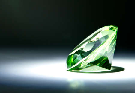 Faceted round cut green gemstone painted with light