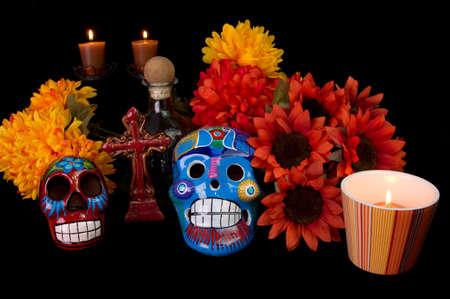 Dia デ ロス ムエルトス日で死んで変更の装飾砂糖頭蓋骨、マリーゴールドの花、ろうそく、およびクロス伝統的なメキシコを提供している愛する人