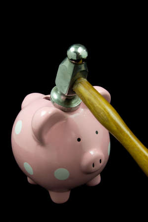 Pink polka dot piggy bank getting hit with hammer black background photo