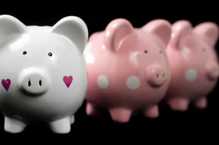 Three little piggy banks lined up. Unique white heart piggy in focus against black background