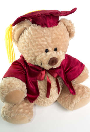 Teddy bear in red regalia and graduation cap. On white background