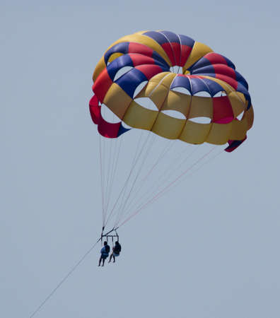 Couple in colorful parasail  parasailing over the pacific ocean