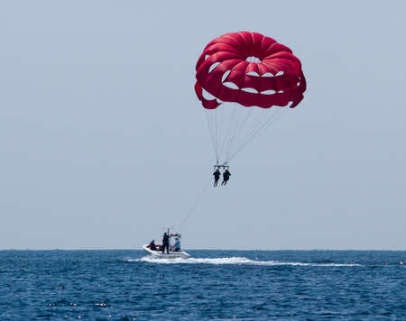 Flying over the ocean in a red parasail