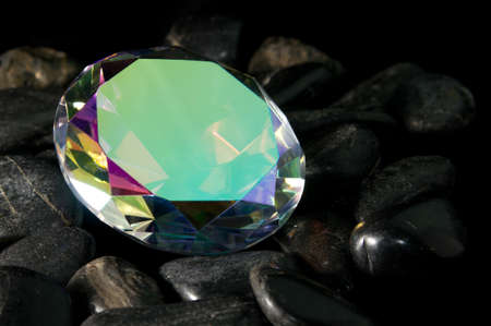 Mystic topaz round cut faceted gemstone sitting on rocks
