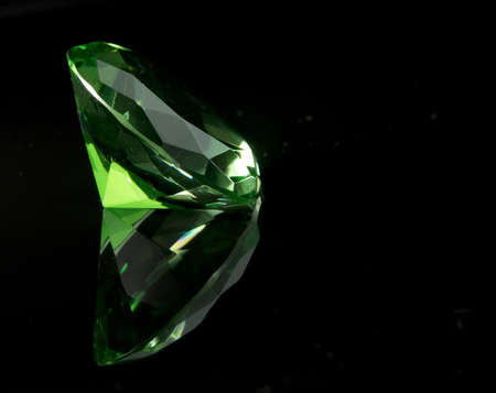 Emerald green round cut faceted gemstone on black background with reflection