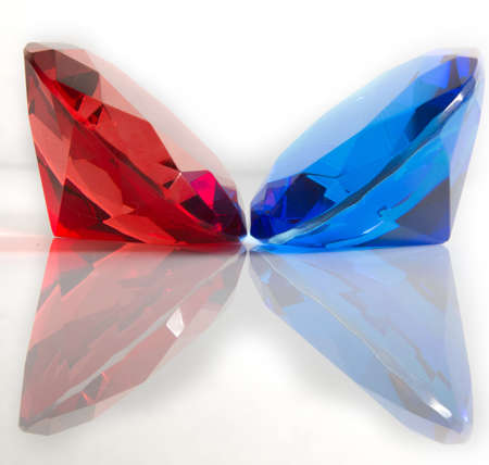 Red and blue round cut faceted gemstones on white background with reflection photo