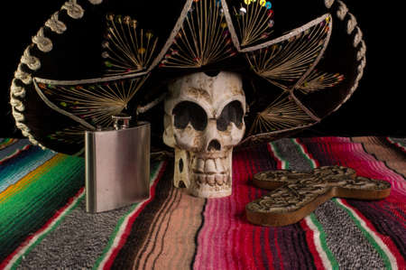 dia de los muertos: Day of The Dead  Dia de los Muertos  skull with with decorative cross, tequila flask on a traditional mexican blanket