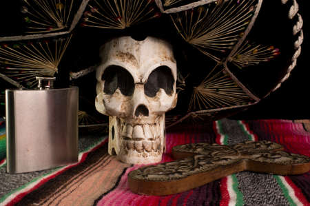 Day of The Dead  Dia de los Muertos  skull with with decorative cross, tequila flask on a traditional mexican blanket  Stock Photo - 14989308