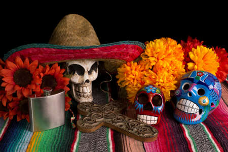 Traditional Dia De Los Muertos  Day of the Dead  alter offering  With marigold   red sunflowers, colorful lumineras, decorative cross, tequila flask,   skull wearing Mexican sombreo  Stock Photo