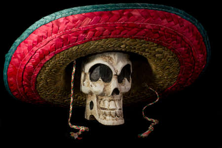Dia De Los Muertos  Day of the Dead  skull wearing colorful Mexican sombrero on isolated on black background Stock Photo