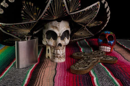 Day of The Dead  Dia de los Muertos  skull with with decorative cross, tequila flask on a traditional mexican blanket Stock Photo - 14989326