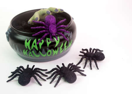 Creepy green hand emerging from Halloween bowl filled with spiders. Isolated on white background photo