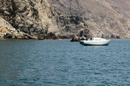 isthmus: Old rusty white boat moored off the coast of Catalina Island. Rugged rocky land in background