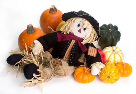 cinderella pumpkin: Harvest scarecrow laying on a bed squash, fairytale, cinderella, and Halloween pumpkins. Stock Photo