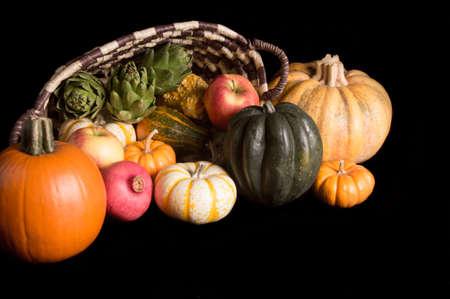 cinderella pumpkin: Cornucopia of fresh pumpkins, squash, apples and pomegranet isolated on black background