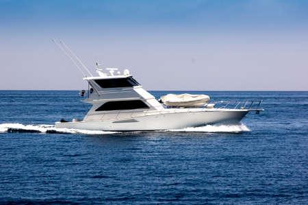 White sportfisher yacht underway.