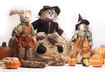 cinderella pumpkin: Scarecrow family on haystack with pumpkins, Indian corn, wheat stalks, gourds, and squash. Isolated on white background