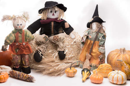 Scarecrow family on haystack with pumpkins, Indian corn, wheat stalks, gourds, and squash. Isolated on white background photo