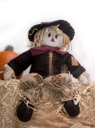Scarecrows on haystack with pumpkin photo