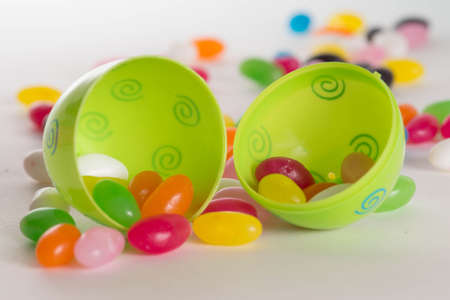 Decorated plastic Easter egg open with colorful jelly beans out of focus in background. Isolated on white background  with light shadow Stock Photo