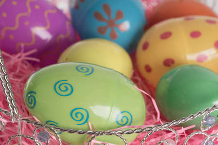 Decorated Easter eggs in Easter basket with pink decorative grass.  Isolated on white background. photo
