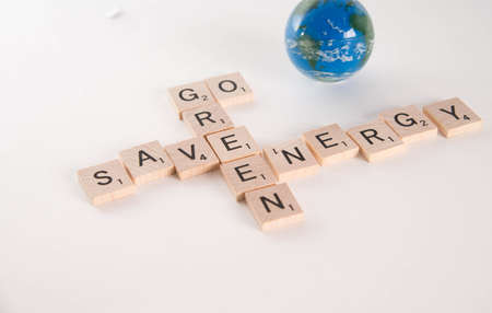 Save Energy, Go Green concept spelled in Scrabble letters with out of focus world globe in the background. Isolated on white background