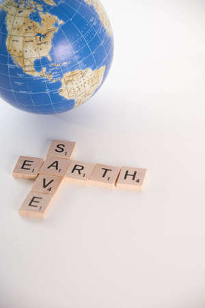 save the earth: Save Earth concept spelled out in Scrabble letters with out of focus world globe in the background. Isolated on white background.