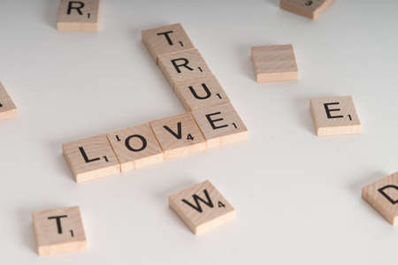 true love: True Love Concept.  Wooden Scrablle letters spelling out phrase True Love. Isolated on white background with light shadow