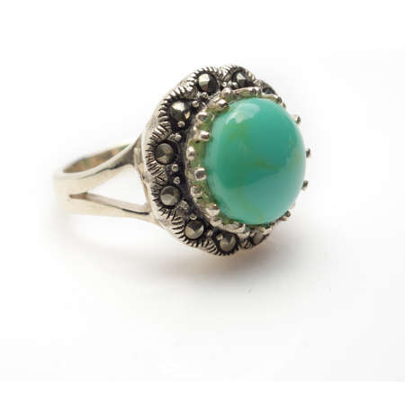 Sterling silver round turquoise cabachon ring with marcasite.  Isolated on white background with light shadow