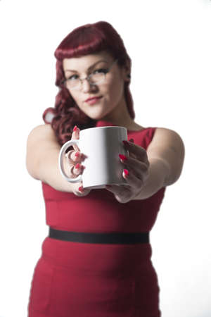 Coffee cup held up with out of focus red headed sexy business woman in the background. Isolated on white background