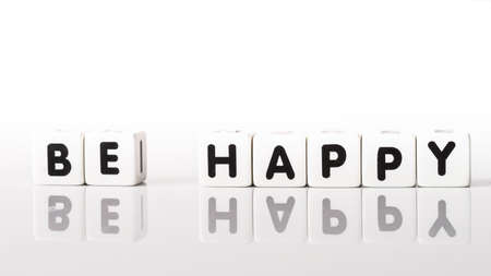 Be Happy spelled in black letters reflected on white background Reklamní fotografie