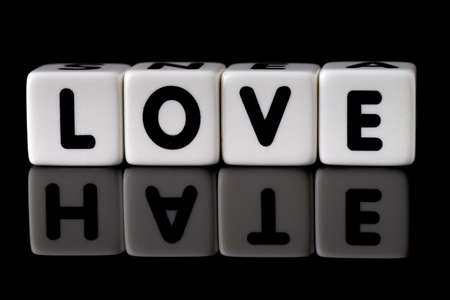 Love spelled in dice with the word hate reflected on black isolated background Reklamní fotografie