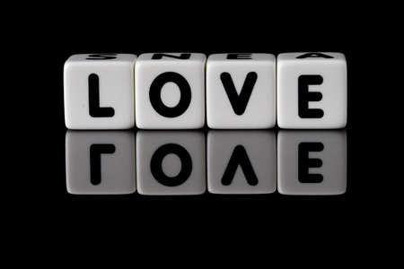 Love spelled in dice with the word hate reflected on white isolated background