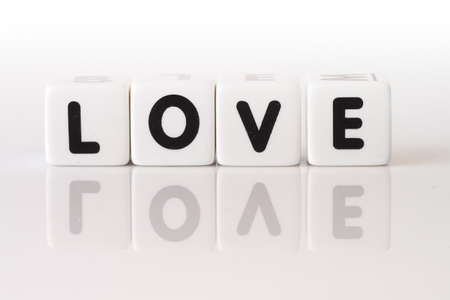 The word love spelled in game dice reflected on isolated white background.