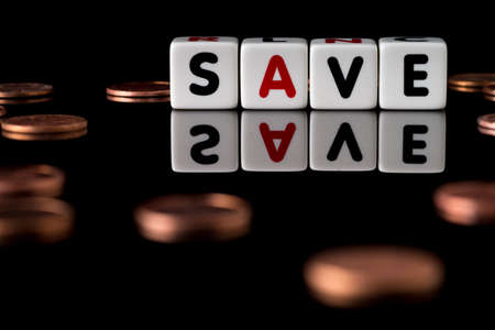 spelled: Save spelled in dice letters reflected on isolated black background with scattered pennies out of focus