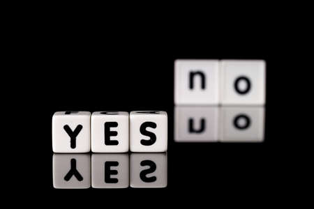 contradict: Yes spelled in dice letters in foreground with the word no out of focus in background  Isolated on black background  Stock Photo