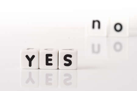 contradict: Yes spelled in dice letters in foreground with the word no out of focus in background  Isolated on white background