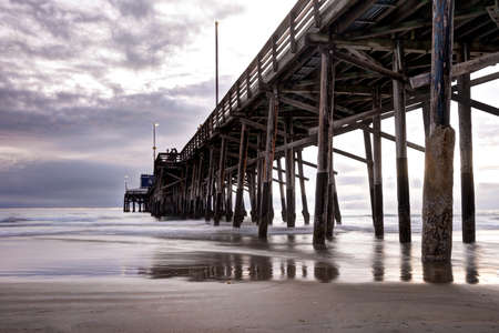 huntington beach: Long exposure captures slow moving waves under The Balboa Pier in scenic Newport Beach, California
