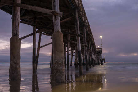 Long exposure captures slow moving waves under The Balboa Pier in scenic Newport Beach, California photo
