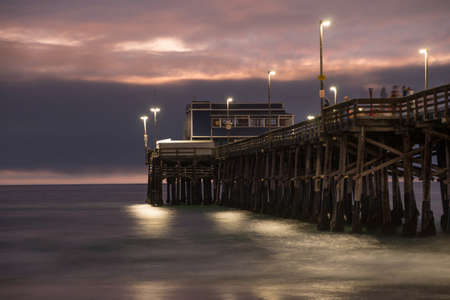 Long exposure captures slow moving waves under The Balboa Pier in scenic Newport Beach, California