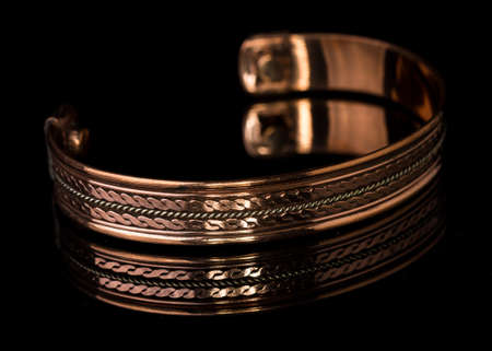 Close up mens copper ornate bracelet isoalted on black background with reflection