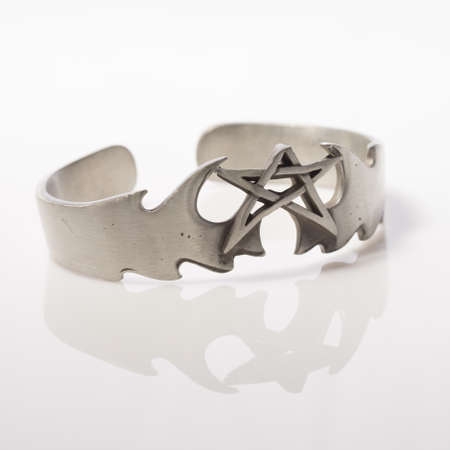 silver jewelry: Star cuff style bracelet on white background with reflection Stock Photo