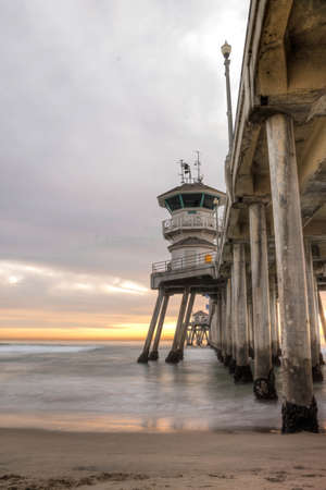 Long exposure captures slow moving waves under The Huntington Beah Pier in Huntington Beach, California photo