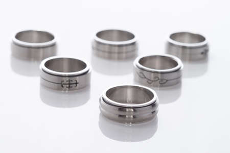 Collection of stainless steel rings on white background with light reflection Imagens